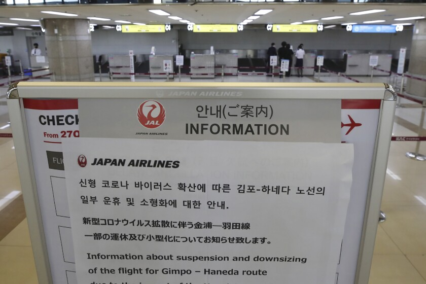 Japan Airlines' notice is placed at Gimpo Airport in Seoul, South Korea, Thursday, March 5, 2020. People around the world girded for months of disruptions from the new virus Thursday as its unrelenting spread brought ballooning infections, economic fallout and sweeping containment measures. (Sun Myung-geon/Yonhap via AP)
