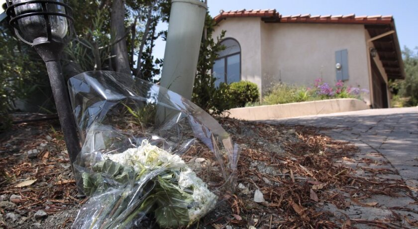 A bouquet of flowers is placed in front of the Rancho Santa Fe home where two women and a teenage girl were found dead Monday.