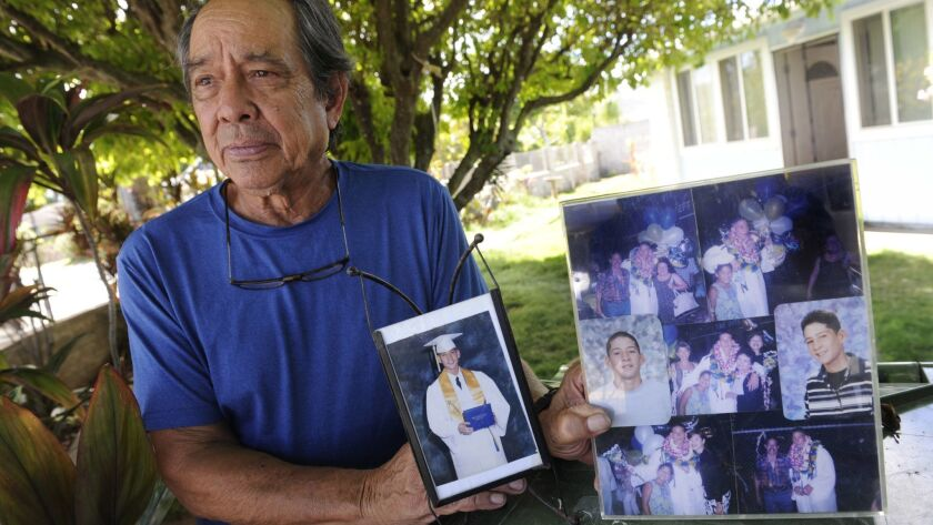 Clifford Kang, father of soldier Ikaika Kang, poses with photos of his son in Kailua, Hawaii, in 2017.
