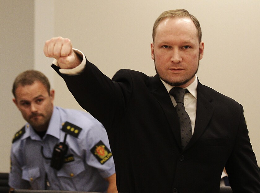 In this Aug. 24, 2012, photo, mass murderer Anders Behring Breivik gives a salute after arriving in a courtroom in Oslo.