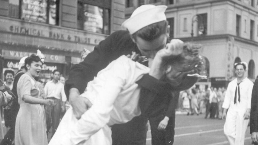 A sailor and a woman kiss in New York's Times Square, as people celebrate the end of World War II on Aug. 14, 1945. The sailor, George Mendonsa, has died.