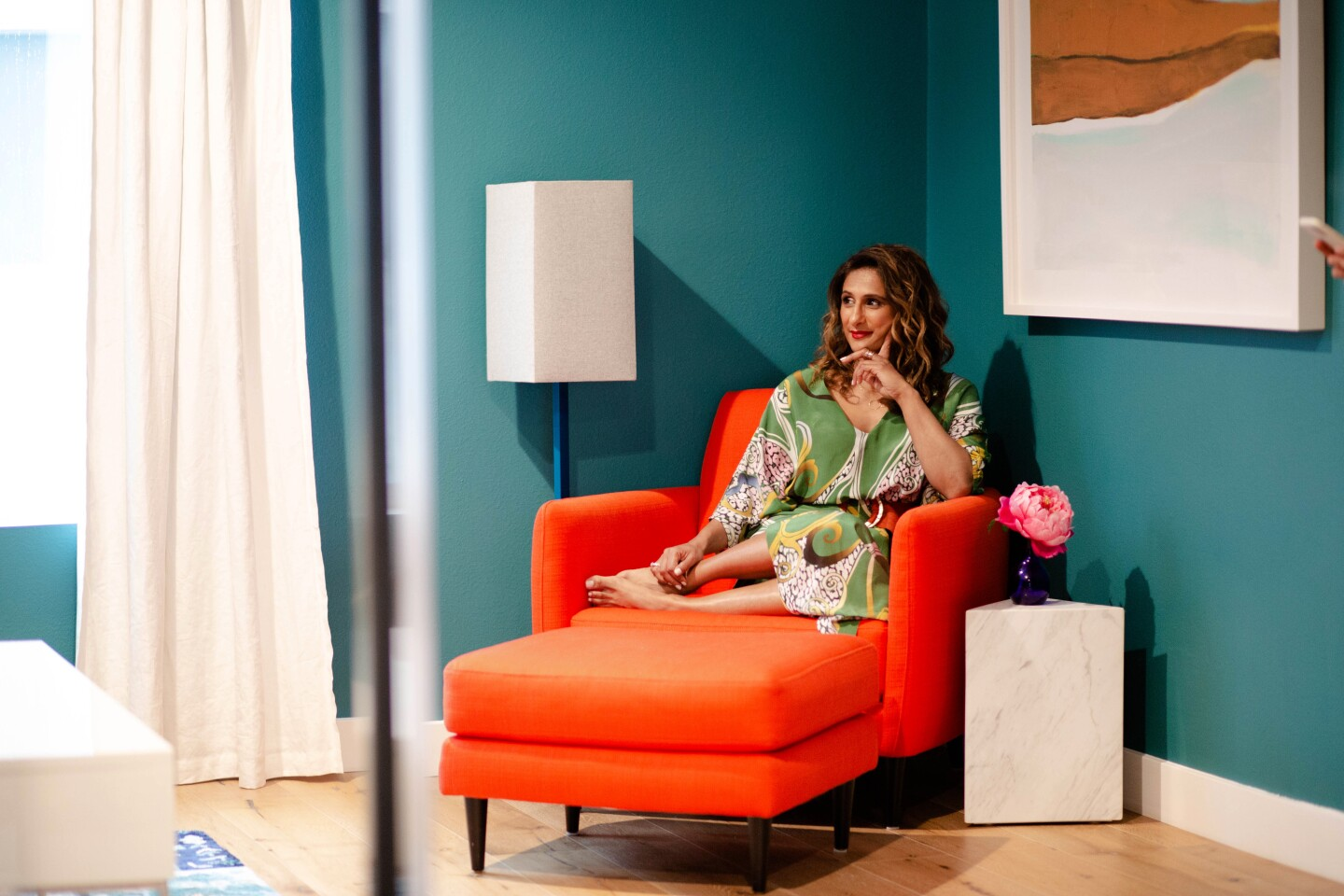 Color - and lots of it - was the goal for actress Sarayu Blue when she converted a guest room in her Studio City home into a personal retreat of sorts. She painted the walls a deep turquoise, anchored one corner with a burnished orange lounge chair, laid down a floral teal rug from Anthropologie and set out vases, which she keeps filled with fresh bouquets. Photographed March 12, 2020. (Jesse Goddard / For The Times)