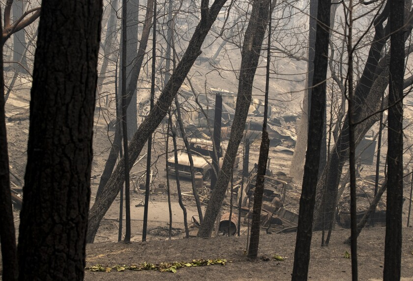 Burned vehicles sit Friday in front of a home destroyed in the North Complex fire.