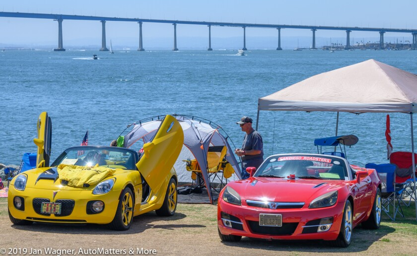 The car show with the Coronado Bay Bridge in the background