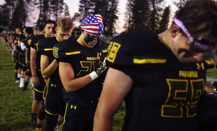Lukas Hartley, second from right, and the Paradise High football team return to field for first time since fire leveled the town last year.