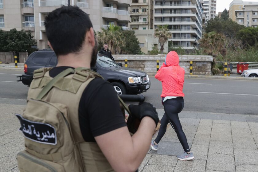A Lebanese intelligence officer asks a jogger to clear the street in Beirut after authorities ordered shops to close for two weeks to fight the coronavirus.