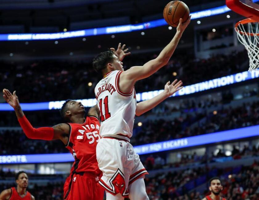 El jugador Doug McDermott (d) de Bulls intenta anotar ante Delon Wright (i) de Raptors hoy, martes 14 de febrero de 2017, durante un partido de la NBA disputado en el United Center de Chicago, Illinois (EE.UU.). EFE