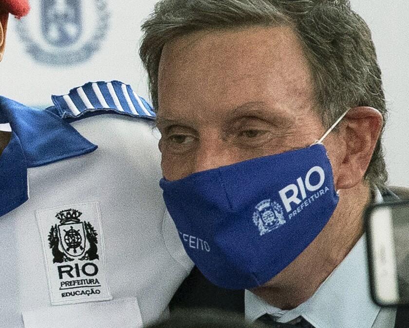 """Rio de Janeiro Mayor Marcelo Crivella in a mask with """"Rio Prefeitura"""" on it."""