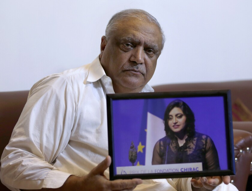 FILE - In this Thursday, Oct. 17, 2019 file photo, Professor Mohammad Ismail, father of a Pakistani human rights activist Gulalai Ismail, displays a photo at his home in Islamabad, Pakistan. A Pakistani lawyer says on Friday, Nov. 1, 2019, a court has adjourned the bail hearing for the father of an exiled activist, who faces trial for supporting a minority Pashtun movement. (AP Photo/Anjum Naveed,File)
