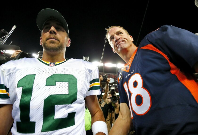 Denver Broncos quarterback Peyton Manning (18) and Green Bay Packers quarterback Aaron Rodgers (12) meet at midfield after an NFL football game, Sunday, Nov. 1, 2015, in Denver. The Broncos won 29-10 to improve to 7-0. (AP Photo/Jack Dempsey)
