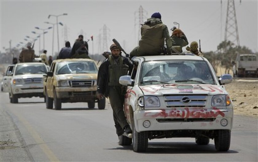Rebel fighters retreat out of Ajdabiya during an advance by pro-Gadhafi forces, on the outskirts of Ajdabiya, Libya Saturday, April 9, 2011. Government soldiers and rebel gunmen battled in the streets of the key front-line city of Ajdabiya Saturday after the Libyan military used shelling and guerrilla-style tactics to open its most serious push into opposition territory since international airstrikes began. (AP Photo/Ben Curtis)
