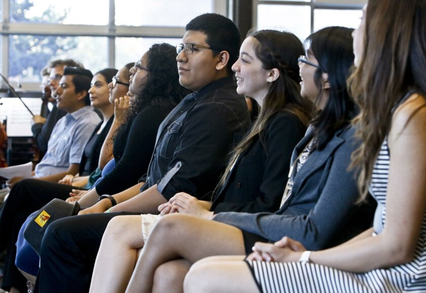 "Scholars from the Queztal Mama Scholar program listen during their ""graduation"" ceremony April 15 at High Tech High in San Marcos. The program takes a select group of high-performing, low-income students and guides them through the college admissions and scholarship application process."