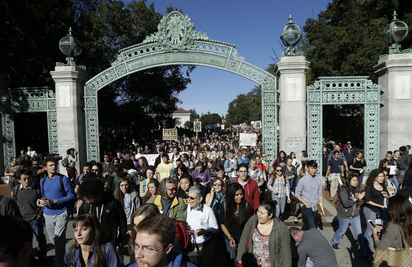 FILE - In this Nov. 24, 2014, file photo, students march under Sather Gate during a tuition-hike protest at the University of California in Berkeley, Calif. University of California regents on Thursday, July 22, will take up a multi-year tuition increase proposal that officials say is needed to keep campuses competitive, increase aid for low-income students and give families some financial predictability. (AP Photo/Jeff Chiu, File)