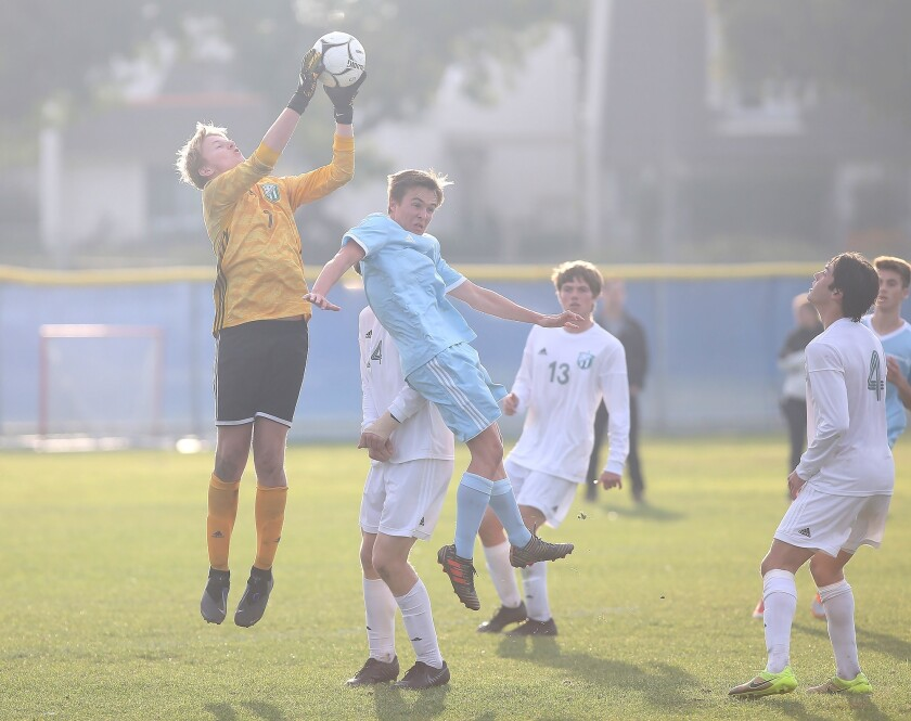Edison goalie Bennet Flory, in yellow, makes a save in Surf League soccer match against Edison on Fr