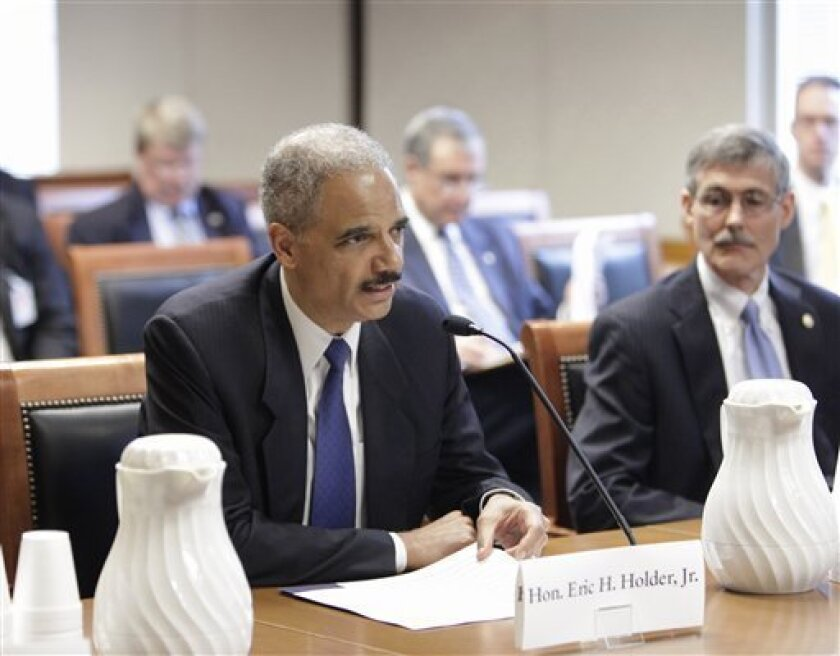 Attorney General Eric Holder testifies before the U.S. Sentencing Commission, Wednesday, June 1, 2011,, at the Thurgood Marshall Federal Judiciary Building in Washington. At right is Acting Director of the Federal Bureau of Prisons Thomas R. Kane. (AP Photo/J. Scott Applewhite)