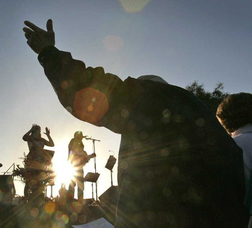 Michael Riney of Encinitas raised his hand in prayer and in song during The Fields' sunrise service yesterday in The Flower Fields.   (Howard Lipin / Union-Tribune)