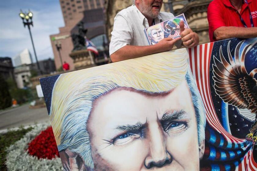 Donald Trump supporter Julian Raven (C) stands behind a painting he made of his candidate before the start of the Republican National Convention in Cleveland, Ohio, USA, 17 July 2016. Numerous protest groups are expected to gather in Cleveland throughout the four-day-long convention. (Protestas, Estados Unidos) EFE/EPA/JIM LO SCALZO