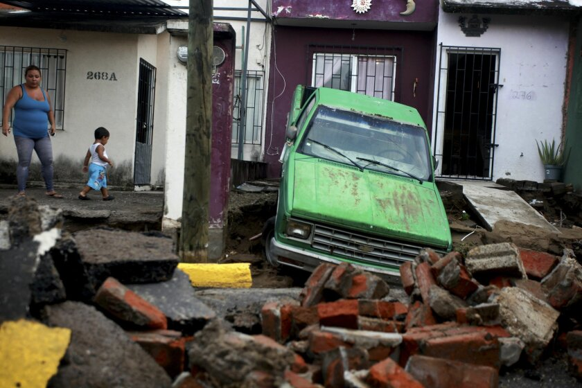 A woman looks at the damage after part of a street and a home collapsed due to heavy rains in the Gulf port city of Veracruz, Mexico, Tuesday Sept. 2, 2014. The Gulf states of Mexico are bracing for more bad weather as Tropical Storm Dolly will cross the coast lat this evening or overnight and continue moving inland over northeastern Mexico on Wednesday. (AP Photo/Felix Marquez)