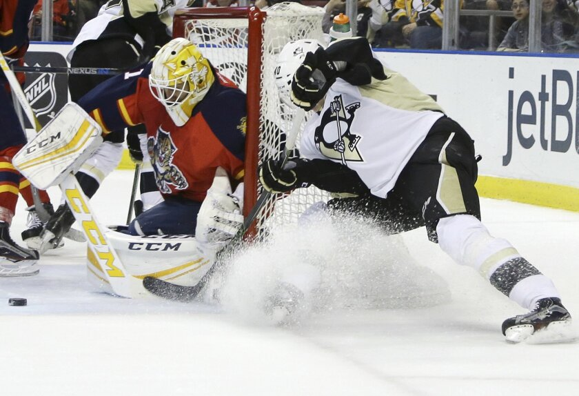Pittsburgh Penguins center Oskar Sundqvist, right, attempts a shot on the goal as Florida Panthers goalie Roberto Luongo, left, defends during the first period of an NHL hockey game, Saturday, Feb. 6, 2016, in Sunrise, Fla. (AP Photo/Lynne Sladky)