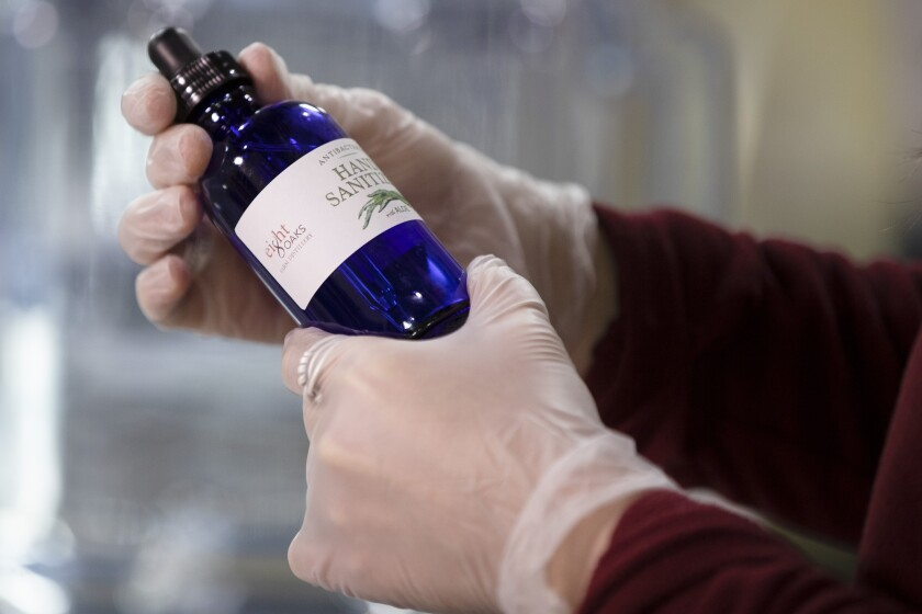 Carly Snyder caps a bottle of hand sanitizer made at the Eight Oaks Farm Distillery in New Tripoli, Pa., Monday, March 16, 2020. The distillery's owner, Chad Butters, grew increasingly angry as he saw the skyrocketing price of hand sanitizer. So he's temporarily converting his operation into a production line for the suddenly hard-to-find, gooey, alcohol-based disinfectant. (AP Photo/Matt Rourke)