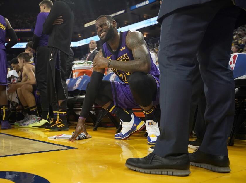 LeBron James, alero de los Lakers de Los Ángeles, hace una mueca tras sufrir un tirón en la ingle izquierda durante el encuentro ante los Warriors de Golden STate, el martes 25 de diciembre de 2018.