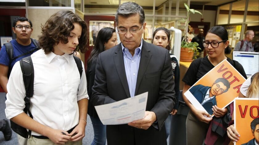 Atty. Gen. Xavier Becerra helps a student fill out a voter registration form in Sacramento in September.