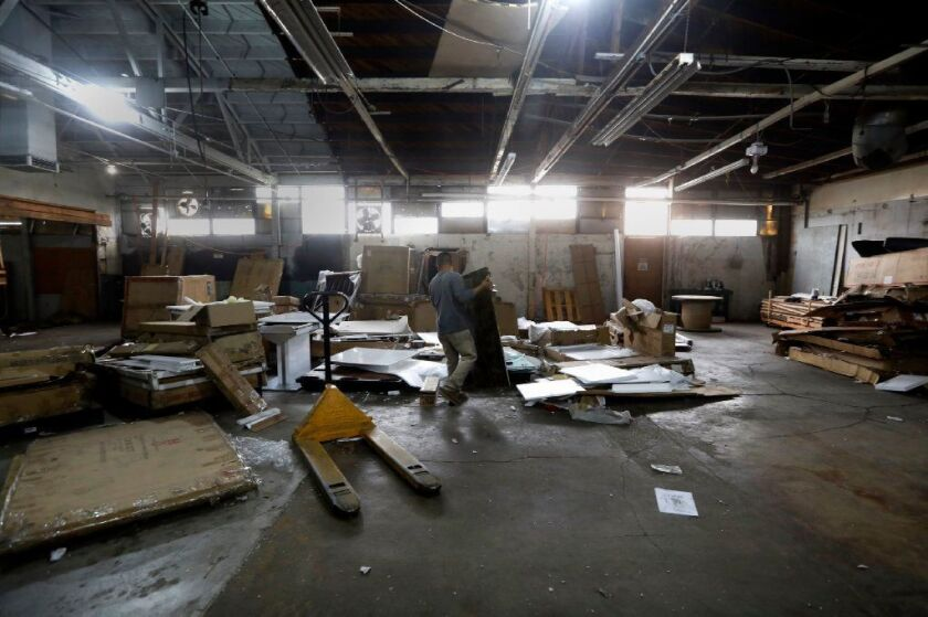 Workers clear out the warehouse that has been approved for marijuana production in El Monte.