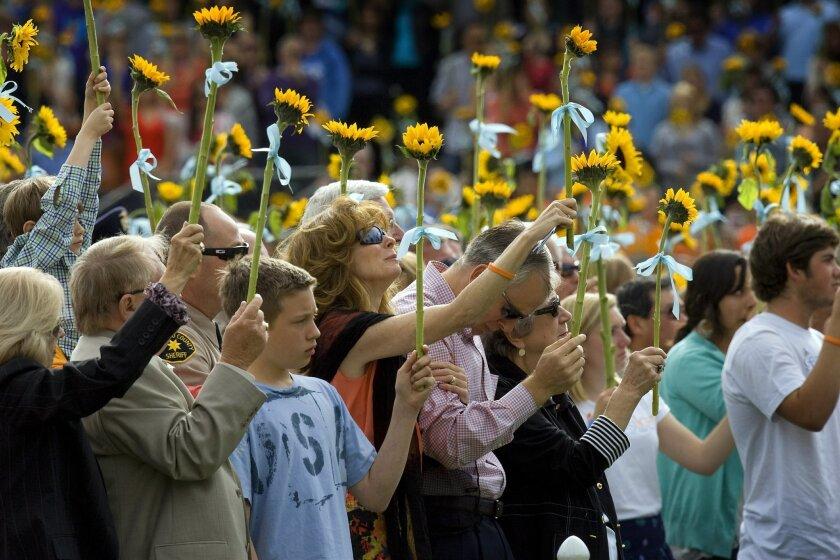 Chelsea King's brother, Tyler (blue shirt); mother, Kelly; and father, Brent, were among thousands of people who raised sunflowers yesterday during the Memorial Celebration for Chelsea King at Poway High School's football stadium.