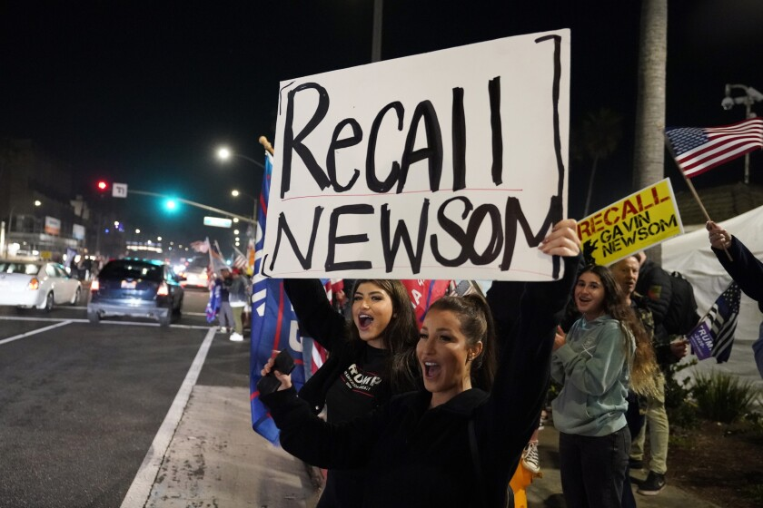 "Protesters in Huntington Beach holds up placards that say ""Recall Newsom"""