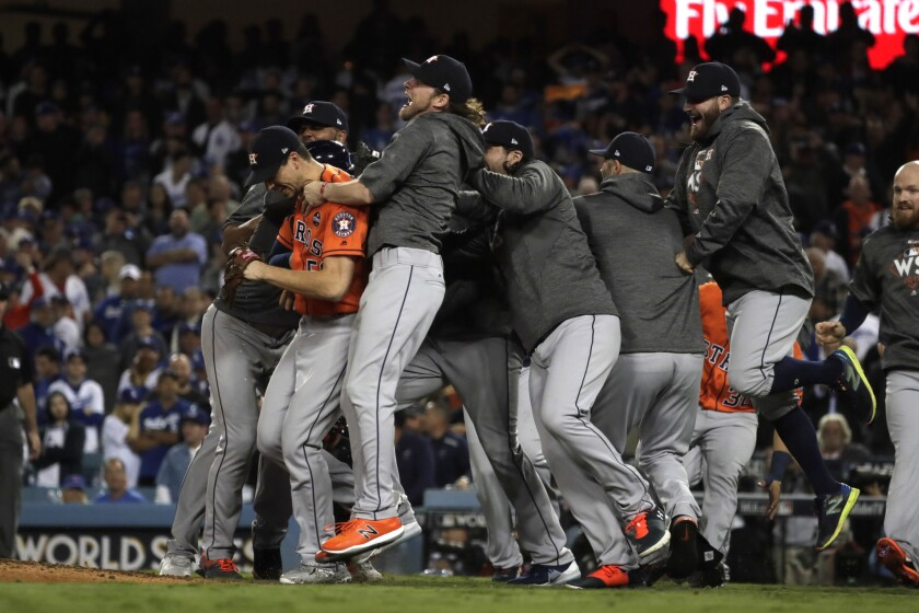 The Astros swarm pitcher Charlie Morton after he held the Dodgers to one run over the last four innings to preserve the win during the 2017 World Series.