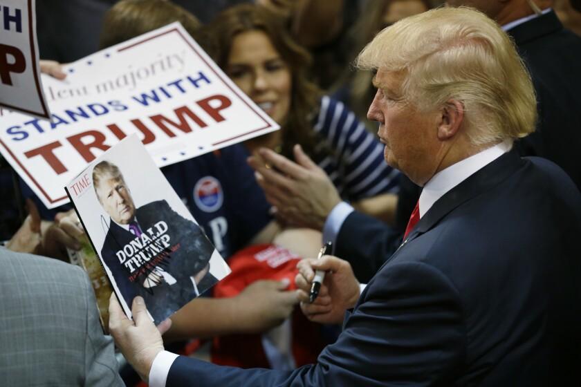 ARCHIVO - En esta fotografía de archivo, el precandidato presidencial republicano Donald Trump observa su foto en la portada de una revista mientras firma autógrafos durante un mitin en Eugene, Oregon. (AP Foto/Ted S. Warren/Archivo)