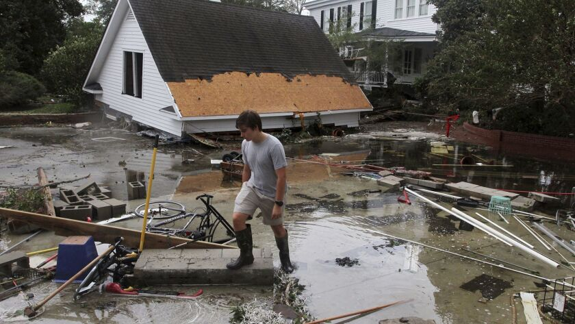 Resident Joseph Eudi looks over flood debris and storm damage at a home on East Front Street in New Bern, N.C.