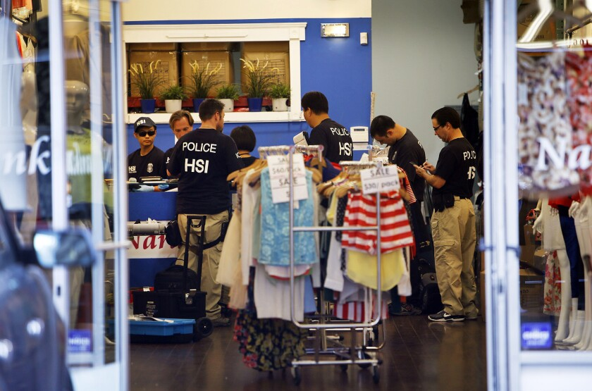 Federal agents gather evidence from a business as they launched a series of raids in the downtown Los Angeles fashion district.