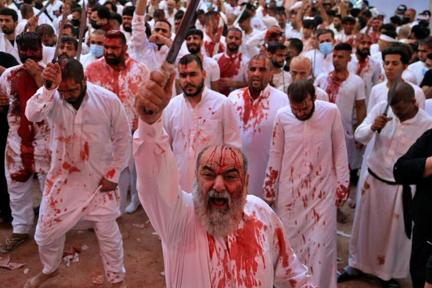 Shiite faithful cut themselves with swords and knives to show their grief during a Muharram procession marking Ashoura inside of the holy shrine of Imam Abbas in Karbala, Iraq, Sunday, Aug. 30, 2020. Shiites mark Ashoura, the tenth day of the month of Muharram, to commemorate the Battle of Karbala when Imam Hussein, a grandson of Prophet Muhammad, was killed. (AP Photo/Anmar Khalil)