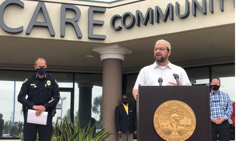 Imam Taha Hassane speaks in front of the CARE Center