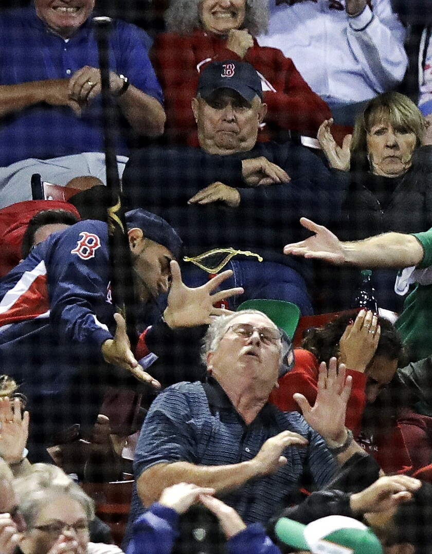 Fans get hit by a bat which flew over the protective screening after Toronto Blue Jays's Devon Travi