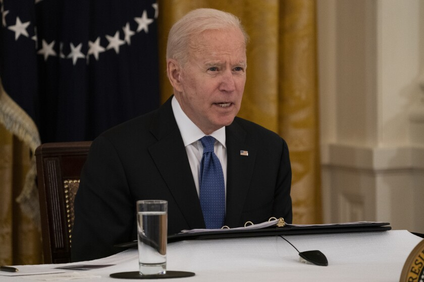 President Biden speaks seated at a table