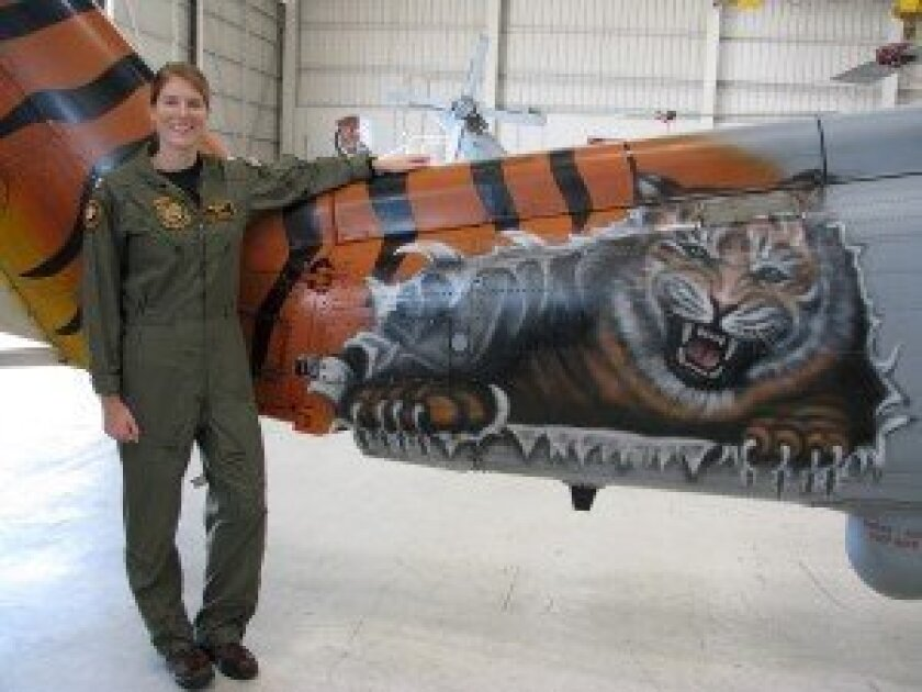 Lt. Darby Clemson Driscoll with one of the 'Battle Cats' helicopters in her fleet squadron at North Island, San Diego. Landing on an aircraft carrier, she said, is a milestone: 'That's when you feel like you're a Navy pilot.'