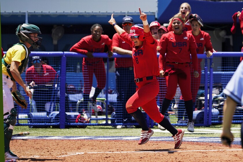 United States' Haylie McCleney scores the game winning run in front of Australia's Belinda White, left, in the eighth inning of a softball game at the 2020 Summer Olympics, Sunday, July 25, 2021, in Yokohama, Japan. (AP Photo/Sue Ogrocki)