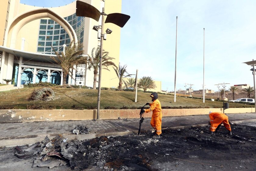 In the wake of a terrorist attack, workers clean debris from the entrance of the Corinthia Hotel in Tripoli, Libya, on Jan. 28.