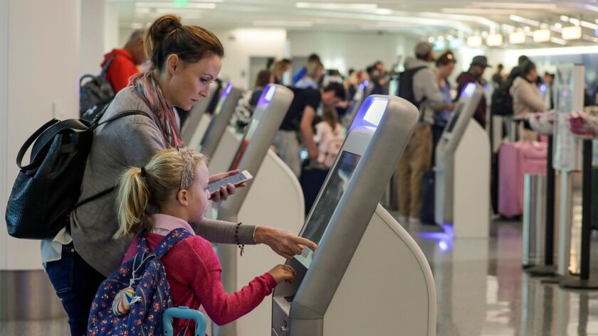 Katy Von Treskow, left, traveling with her 5-year-old daughter, Madeline, uses a check-in kiosk at Los Angeles International Airport. A study found the surfaces of such kiosks are high in bacteria.