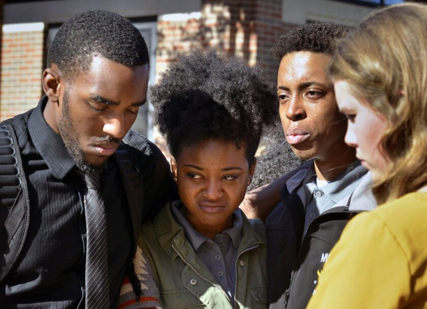 In this Saturday, Nov. 7, 2015, photo, members of the Legion of Black Collegians and the Concerned Student 1950 supporters gather outside the Reynolds Alumni Center after an emotional protest on the University of Missouri campus, in Columbia, Mo. Some campus groups have been protesting the way univ