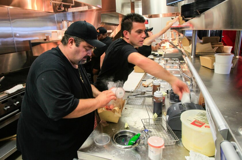 Owner Charlie Boghosian (left) makes a take out meal during the grand opening of Chicken Charlie's Table in 2014.