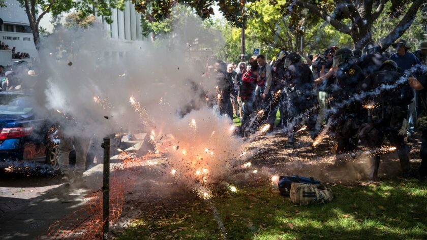 A firework thrown by someone in the crowd explodes at the feet of police and supporters of President Trump as they clash with protesters at an April 15 rally in Berkeley organized by the Trump supporters.