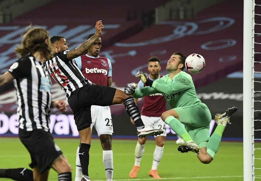 Newcastle's Callum Wilson, second left, scores his side's opening goal during the English Premier League soccer match between West Ham United and Newcastle United at the London Stadium in London, Saturday, Sept. 12, 2020. (Michael Regan/Pool via AP)