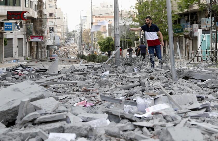 Gente revisando los escombros del edificio residencial Yazegi, destruido por un ataque aéreo israelí