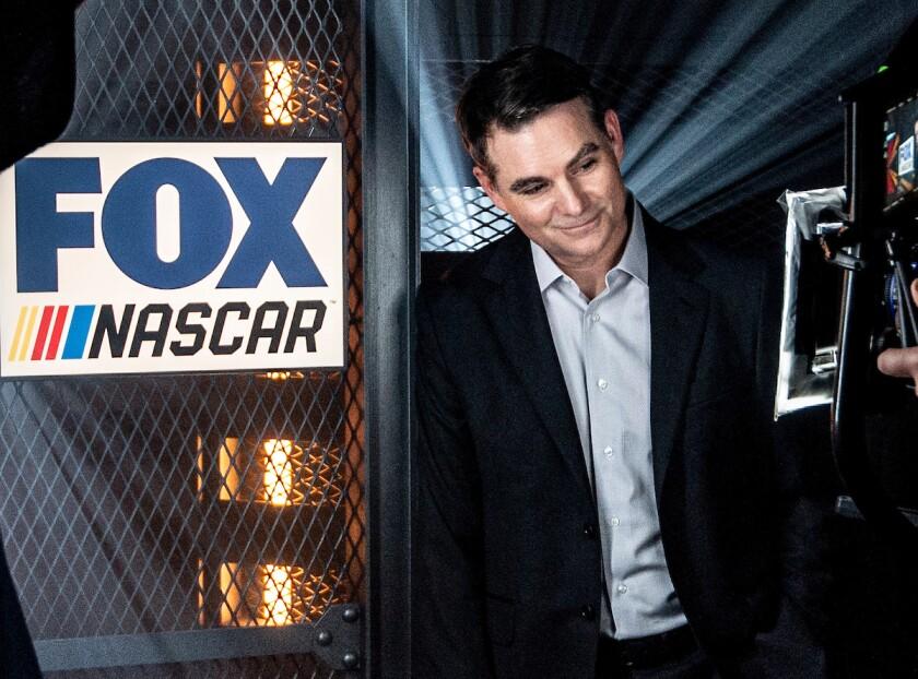 Former NASCAR driver Jeff Gordon stands next to a Fox Sports NASCAR sign.
