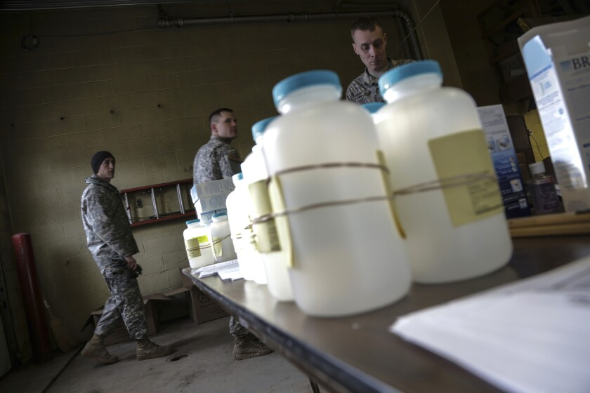 FILE - In this Jan. 18, 2016 file photo, water analysis test kits for Flint, Mich., residents to pick up for lead testing in their drinking water are set out on a table at Flint Fire Department Station No. 1 as members of the U.S. Army National Guard 125th Infantry Battalion wait to help residents. Flint has taken important steps toward resolving the lead contamination crisis that made the impoverished Michigan city a symbol of the drinking water problems that plague many U.S. communities, officials said Monday, Dec. 7, 2020. (Ryan Garza/Detroit Free Press via AP, File)