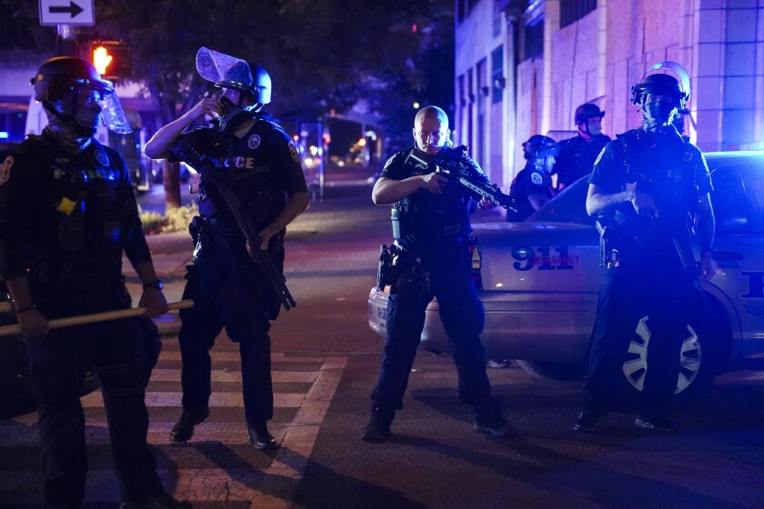 FILE - Police stand guard on the perimeter of a crime scene after a police officer was shot, Wednesday, Sept. 23, 2020, in Louisville, Ky. Recent shootings of police officers and protests that have left scores of officers injured are stark reminders of the dangers facing law enforcement around a country grappling with police killings of African Americans. (AP Photo/John Minchillo, File)
