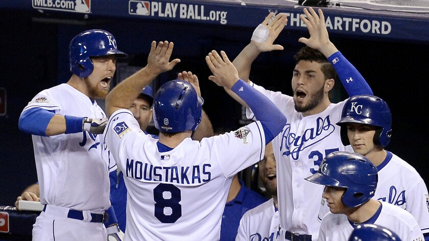Royals third baseman Mike Moustakas (8) celebrates with teammates after scoring against the Blue Jays on a single by Alex Rios in the seventh inning Friday night.